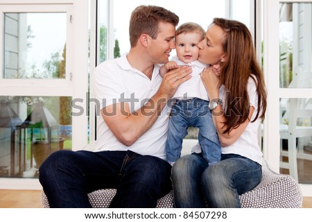 Mother and father hugging and kissing son in home interior - stock photo