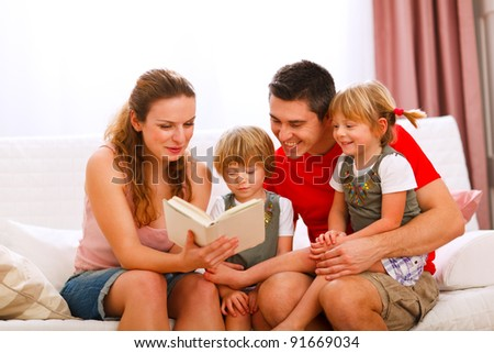 Mother and father reading to twins daughters