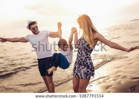 Mother and father with their son walking together on a quiet beach. #1087791554