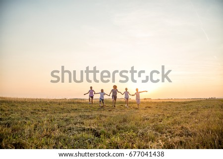 Mother and four kids having fun in the field, holding hands and running towards camera outdoors,  at summer field at sunset. The group is at the distance. They are wearing casual clothes.