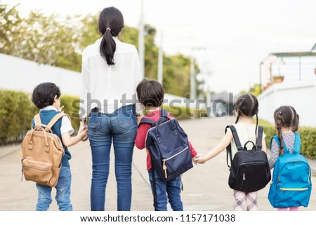 Mother and four kids holding hands are walking to school bus.Kids shoulder schoolbag.Back to school,primary school,Kindergarten,Group primary school kids walking to school.