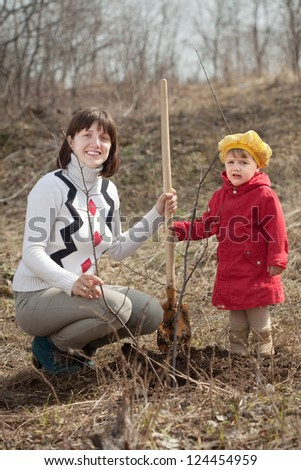 Mother and her baby girl planting tree