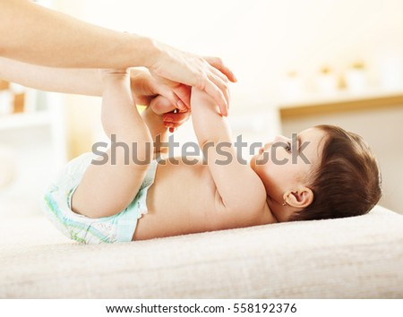 Mother and her baby girl.Playing and changing diapers. #558192376