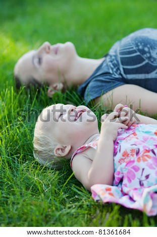 Mother and her baby lying on the grass