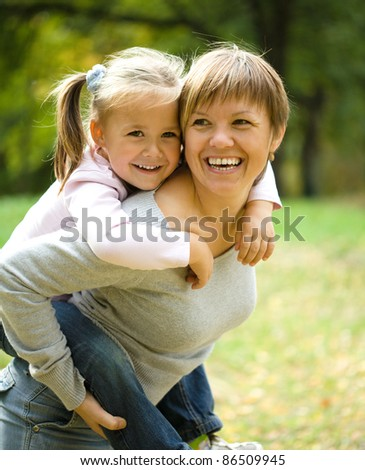 Mother and her child are playing in autumn park - stock photo