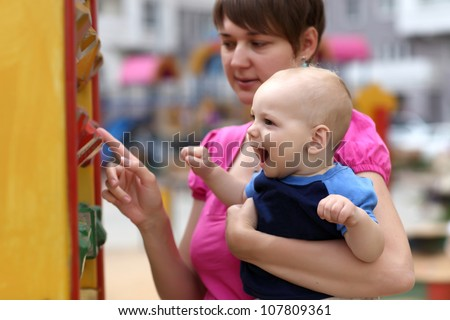 Mother and her child are playing with wooden blocks at playground