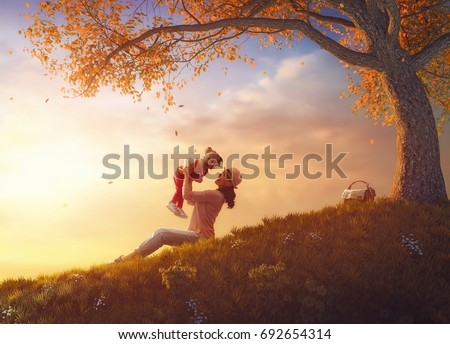 Mother and her child girl are playing together on autumn walk in nature outside. Happy loving family are having fun.