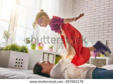 Mother and her child girl playing together. Girl in an Superman\'s costume. The child having fun and jumping on the bed.