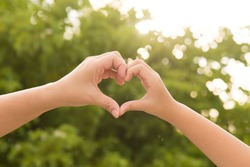 Mother and her child holding hands in heart shape framing on nature background