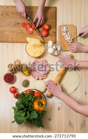 Mother and her children cooking pizza at home. Filling pizza with ingredients. Top view. Overhead view.