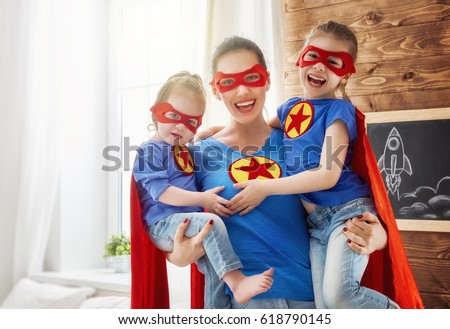 Mother and her children playing together. Girls and mom in Superhero costumes. Mum and kids having fun, smiling and hugging. Family holiday and togetherness.