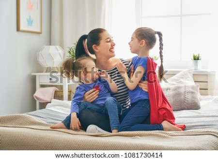 Mother and her children playing together. Mom and girls in Superhero costumes. Mum and kids having fun, smiling and hugging. Family holiday and togetherness. #1081730414