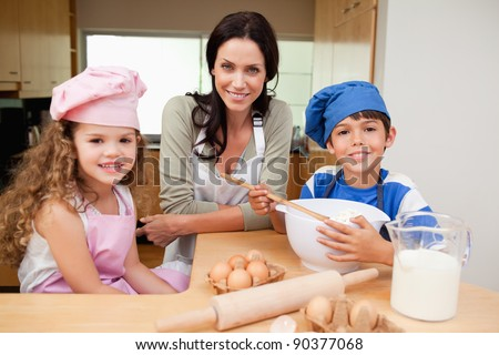 Mother and her children preparing cake together