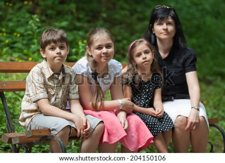 Mother and her children sitting on bench in the park at summer day