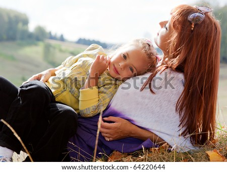 Mother and her daughter are in autumn park