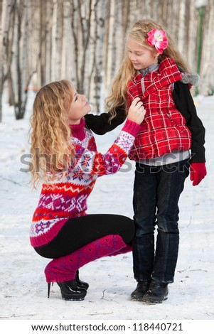 Mother and her daughter are on a walk in park in winter.