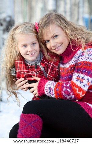 Mother and her daughter are sitting close each other in park in winter. They are happy and are smiling.
