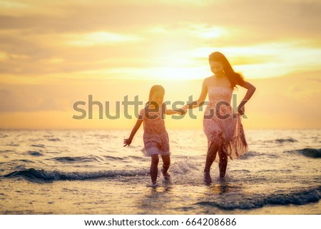 Mother and her daughter are walking happily at the beach at sunset in holiday. #664208686