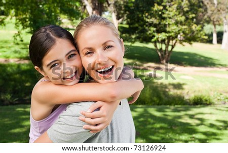 Mother and her daughter laughting in the park - stock photo