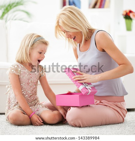 Mother and her daughter opening a pink birthday present.