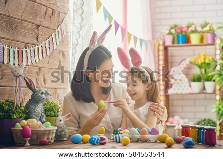 Mother and her daughter painting eggs. Happy family preparing for Easter. Cute little child girl wearing bunny ears. #584553544