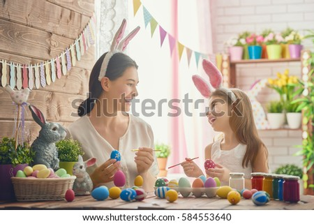 Mother and her daughter painting eggs. Happy family preparing for Easter. Cute little child girl wearing bunny ears. #584553640