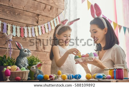 Mother and her daughter painting eggs. Happy family preparing for Easter. Cute little child girl wearing bunny ears. #588109892