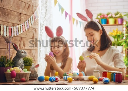 Mother and her daughter painting eggs. Happy family preparing for Easter. Cute little child girl wearing bunny ears. #589077974