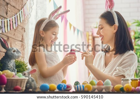Mother and her daughter painting eggs. Happy family preparing for Easter. Cute little child girl wearing bunny ears. #590145410