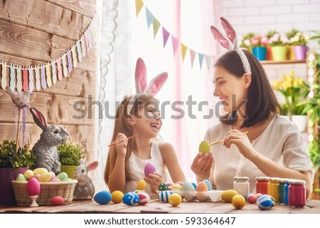 Mother and her daughter painting eggs. Happy family preparing for Easter. Cute little child girl wearing bunny ears. #593364647