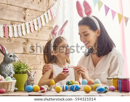 Mother and her daughter painting eggs. Happy family preparing for Easter. Cute little child girl wearing bunny ears. #594321014