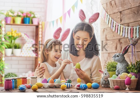 Mother and her daughter painting eggs. Happy family preparing for Easter. Cute little child girl wearing bunny ears. #598835519