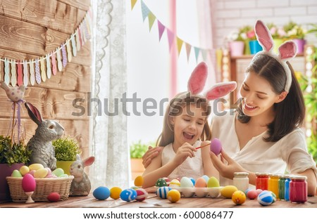 Mother and her daughter painting eggs. Happy family preparing for Easter. Cute little child girl wearing bunny ears. #600086477