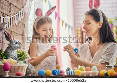 Mother and her daughter painting eggs. Happy family preparing for Easter. Cute little child girl wearing bunny ears. #600086525