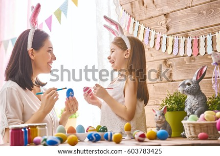 Mother and her daughter painting eggs. Happy family preparing for Easter. Cute little child girl wearing bunny ears. #603783425
