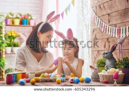 Mother and her daughter painting eggs. Happy family preparing for Easter. Cute little child girl wearing bunny ears. #605343296