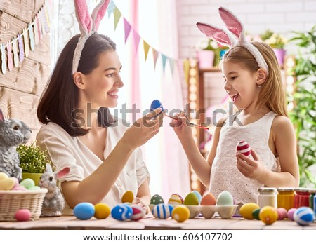 Mother and her daughter painting eggs. Happy family preparing for Easter. Cute little child girl wearing bunny ears. #606107702