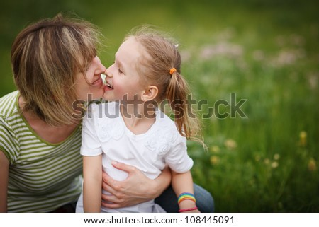 Mother and her daughter playing outdoors nose to nose