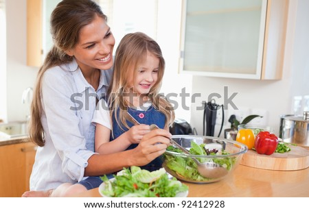 Mother and her daughter preparing a salad in their kitchen