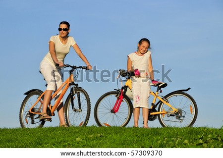 Mother and her daughter riding on a bicycles