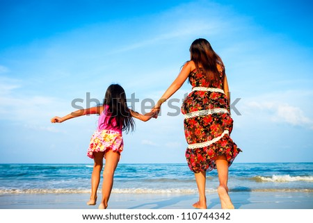 Mother and her daughter running together while holding hands on beach