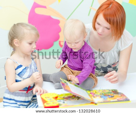 Mother and her daughters reading a book