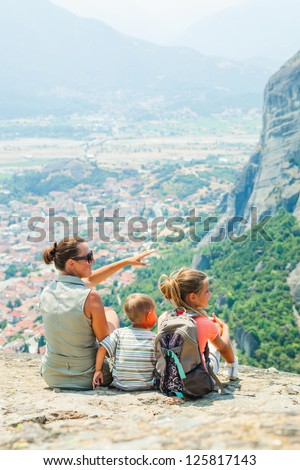 Mother and her kids looking at the town of Kalambaka bird's eye view. Vertical view. Meteora, Greece.