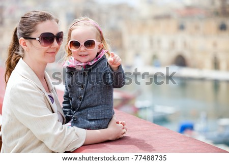 Mother and her little daughter outdoors in city