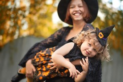 Mother and her little daughter ready for trick or treat, wearing halloween witch costumes. Autumn day outdoors, yellow leaves