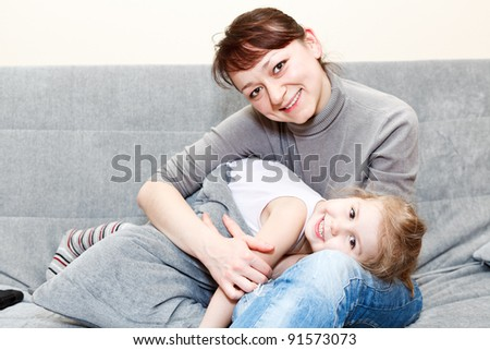 Mother and her little daughter sitting and couch and hugging