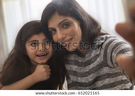 Mother and her little daughter taking selfie with smartphone  #652021165