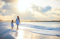 Mother and her little daughter walking along a beach on sunset