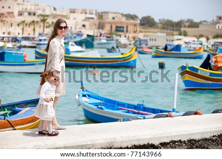 Mother and her little daughter walking in Marsaxlokk village in Malta