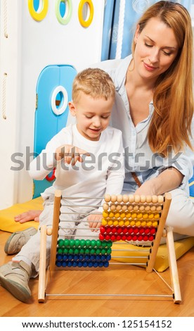 Mother and her little son learning math with abacus